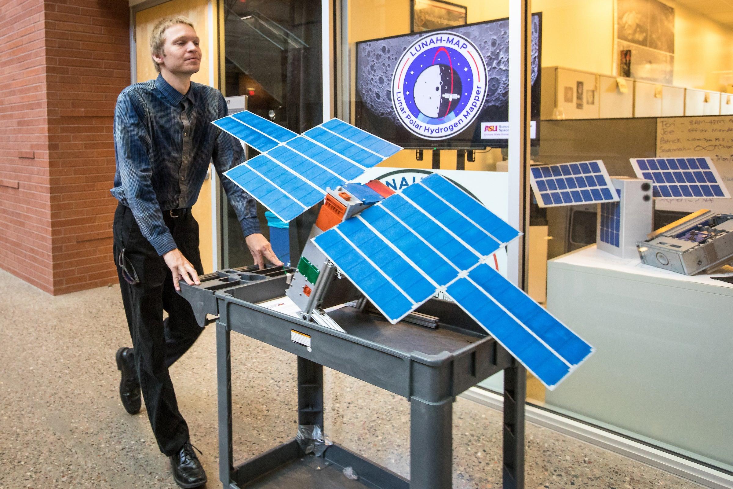 A student wheels a full-scale LunaH-Map model through a hallway