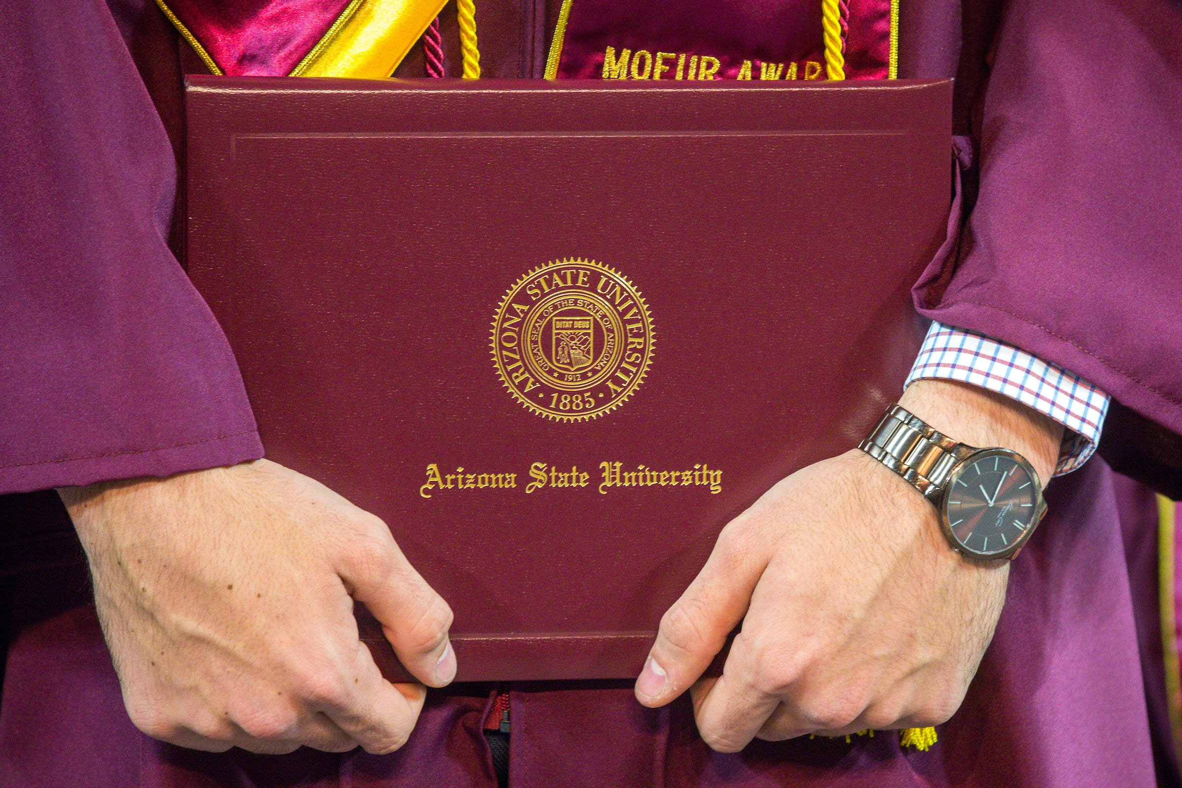 A new graduate holds his diploma