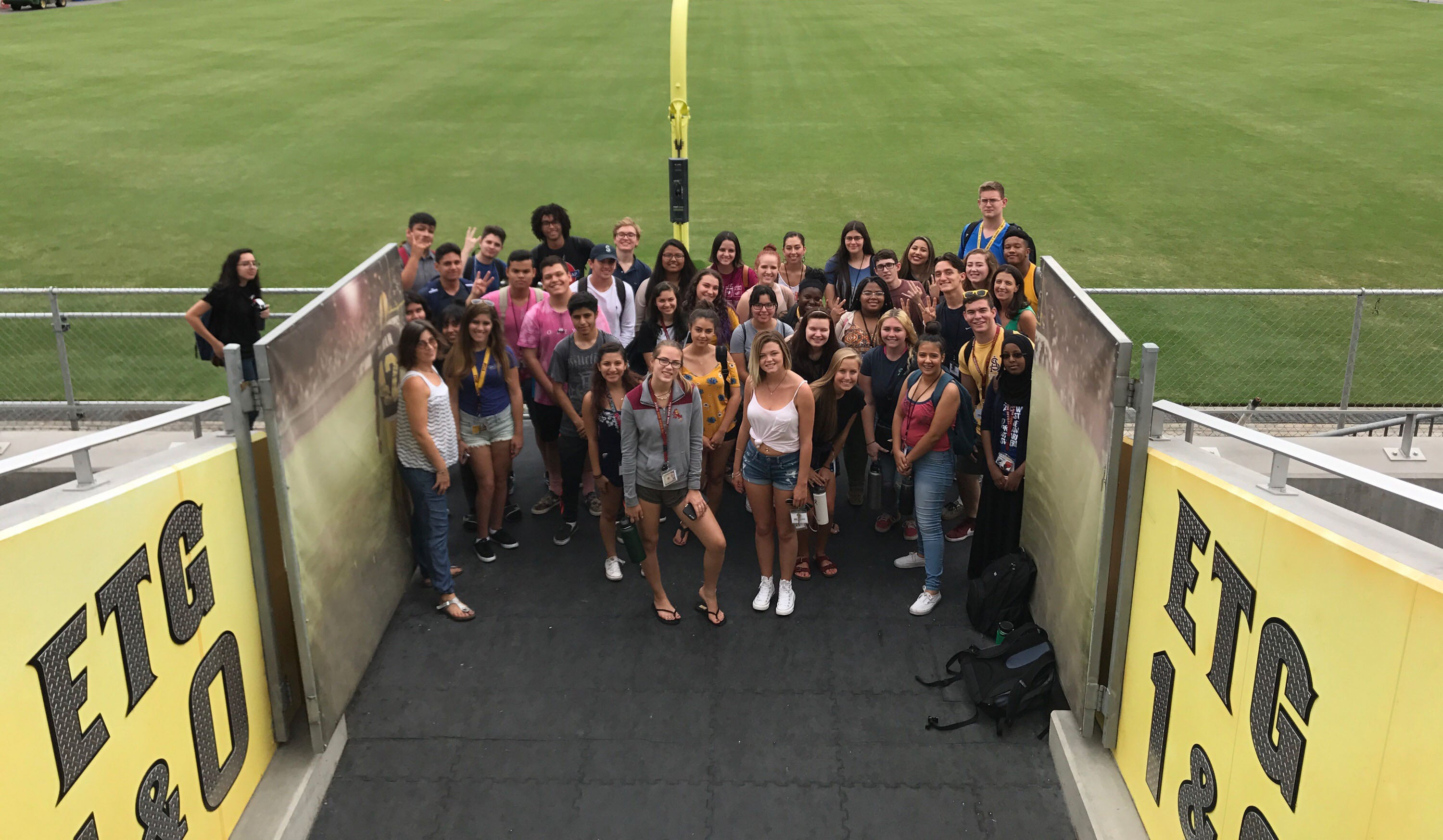 students standing in front of football field