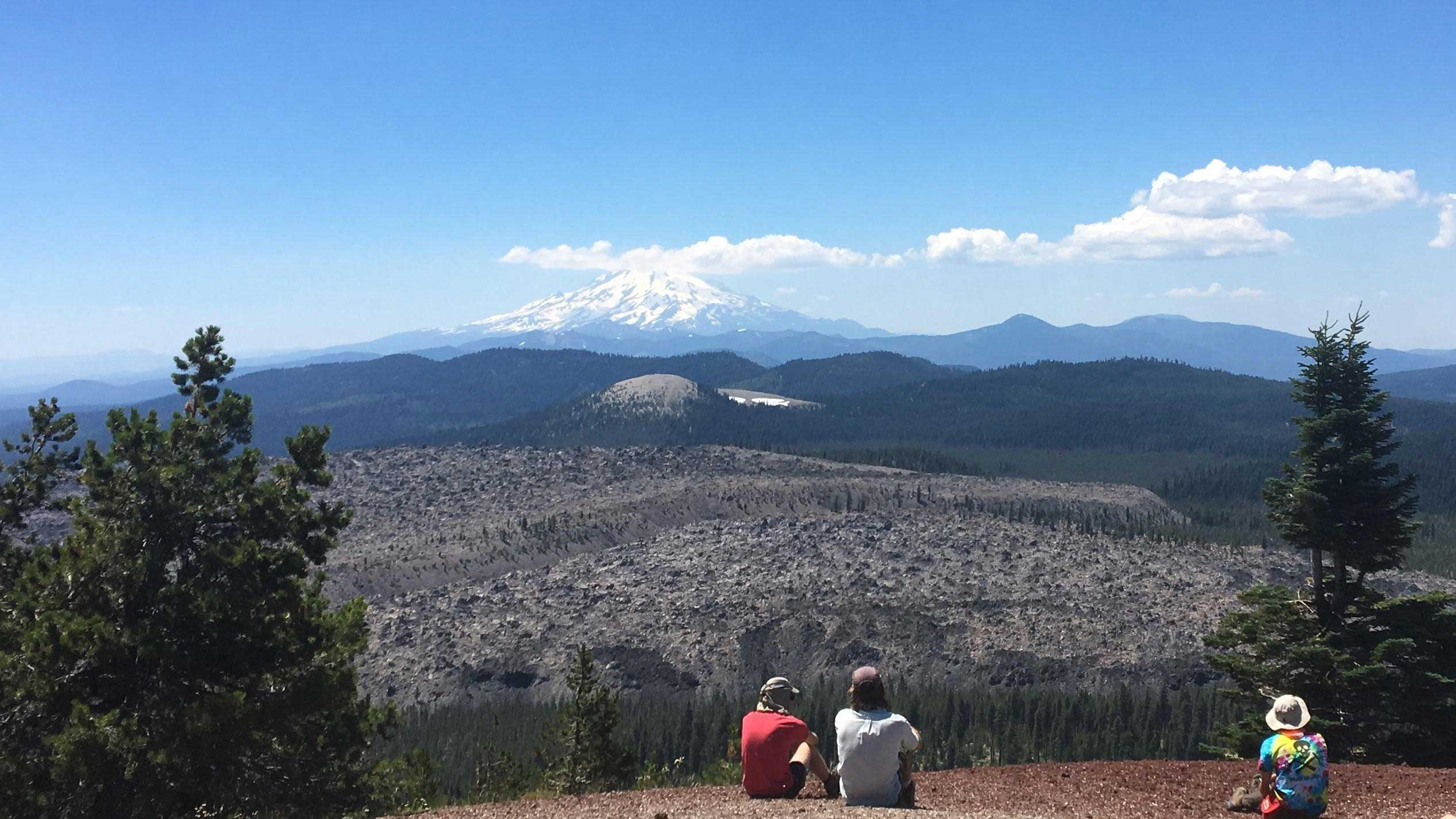 People look at a dormant volcano in the distance
