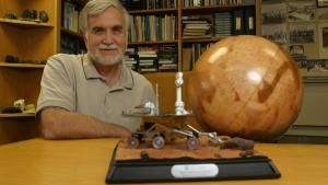 Ronald Greeley sits casually at a desk, a globe at his side and a model of a rover in front and a full book shelf behind him.