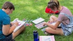 Two students sit crossed legged on a lush green lawn looking over books and homework.
