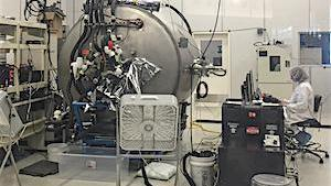 Looking inside a clean room with a large metal circular chamber with an individual wearing  a cleanroom suit sits at a computer nearby.